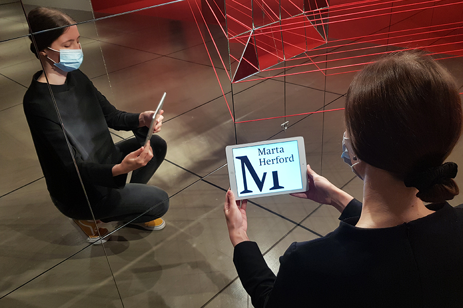 Eine Frau mit einem Tablet hockt vor einer Spiegelfläche. Auf dem Tablet ist das Logo des Museums Marta Herford zu sehen.